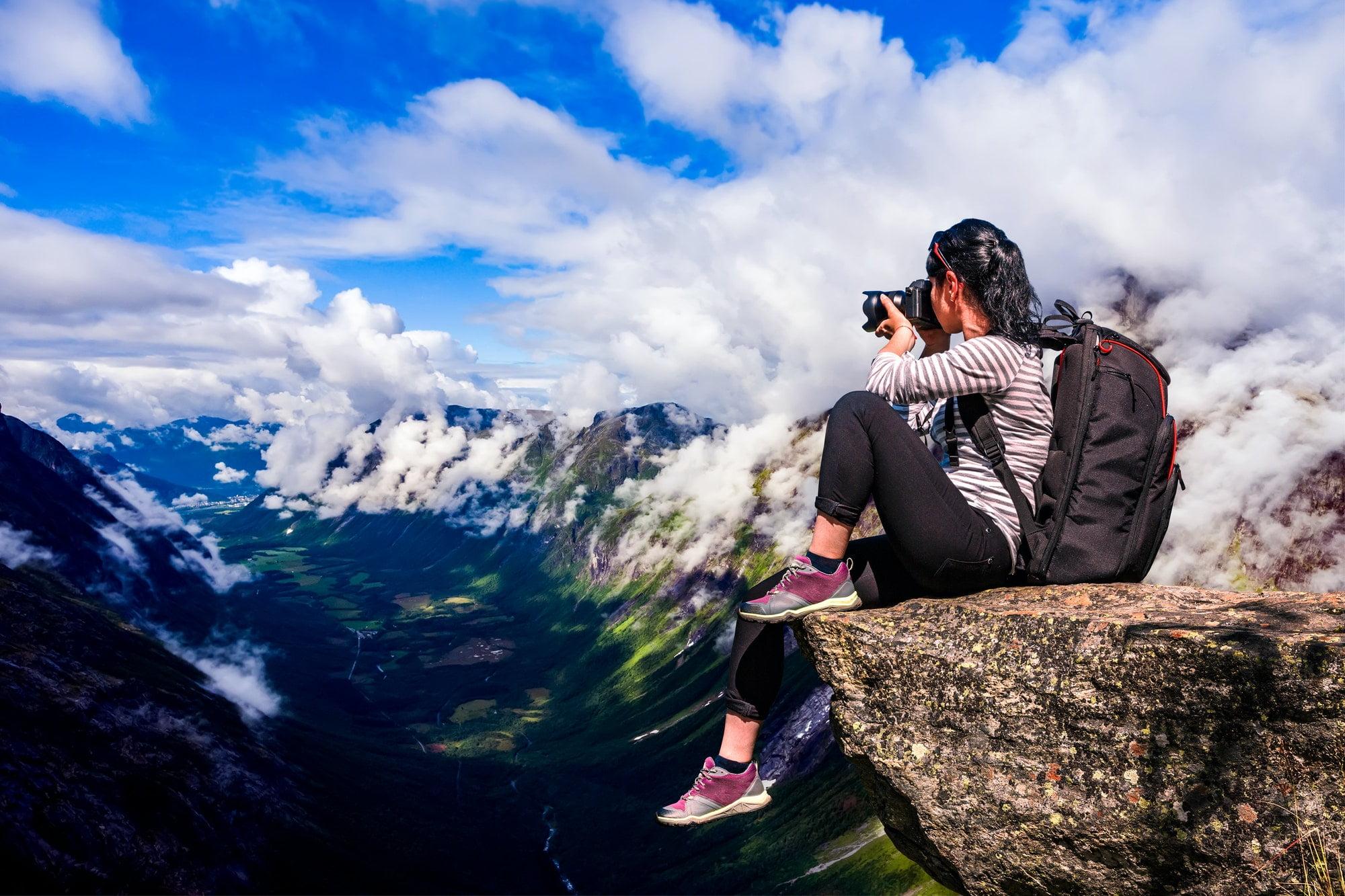 Person som sitter på kanten av et fjell og tar bilde